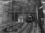 .61152 emerges from the western portal of Woodhead tunnel with a down express in June 1949.Some electrification masts are in place and other materials are lying about