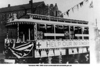 A tram decorated for a fund raising event associated with the infirmary, outside the Queen's Electric Theatre.