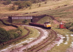 020-The final death throes of the Woodhead Route. On 31st May 1987, 47354 is seen heading westwards with a train of recovered sleepers near Torside crossing