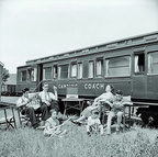 Family at Cheddar station sitting in deckchairs beside a camping coach, 1956